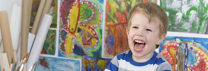excited child with paintings in the background